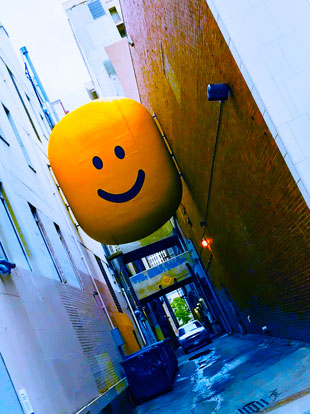 Photo of Artwork Stuart Semple, I should be crying but I just can't let it show (2018) in Denver Alley, Denver, CO, large yellow smiley head